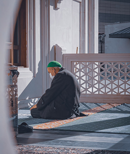 Muslim worshipper at prayer outside mosque