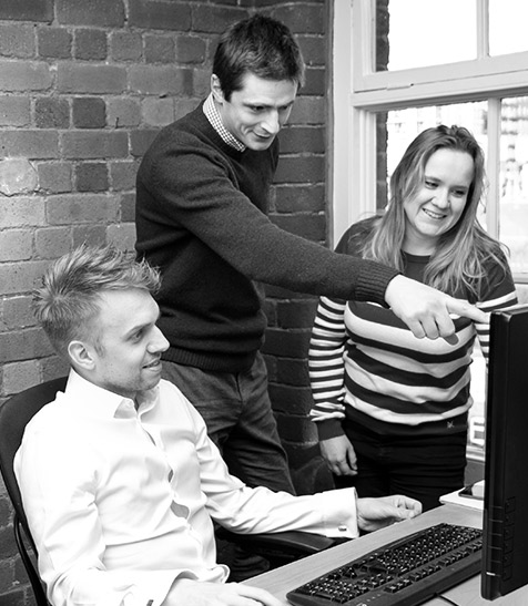 GWD team members in discussion around a computer