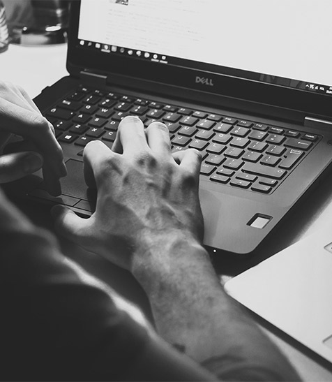 Hands typing on laptop in black and white image