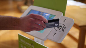 Hand holding credit card against contactless payment donation device